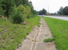 Acidic runoff from a highway cut slope dissolves part of the concrete ditch lini